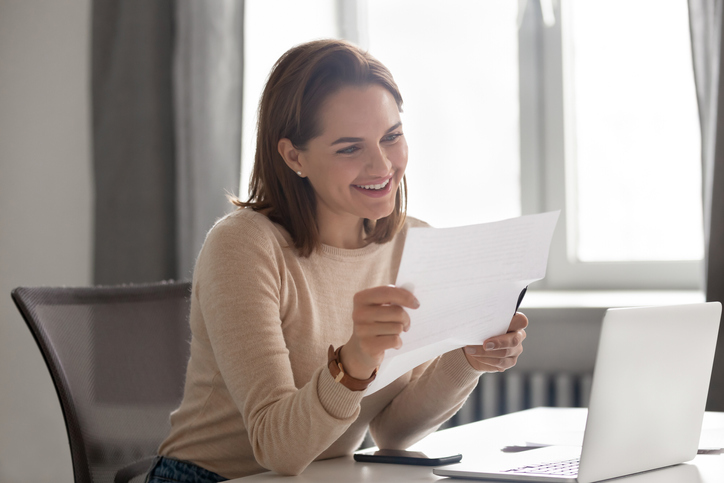 Happy young businesswoman reading great news in paper mail letter